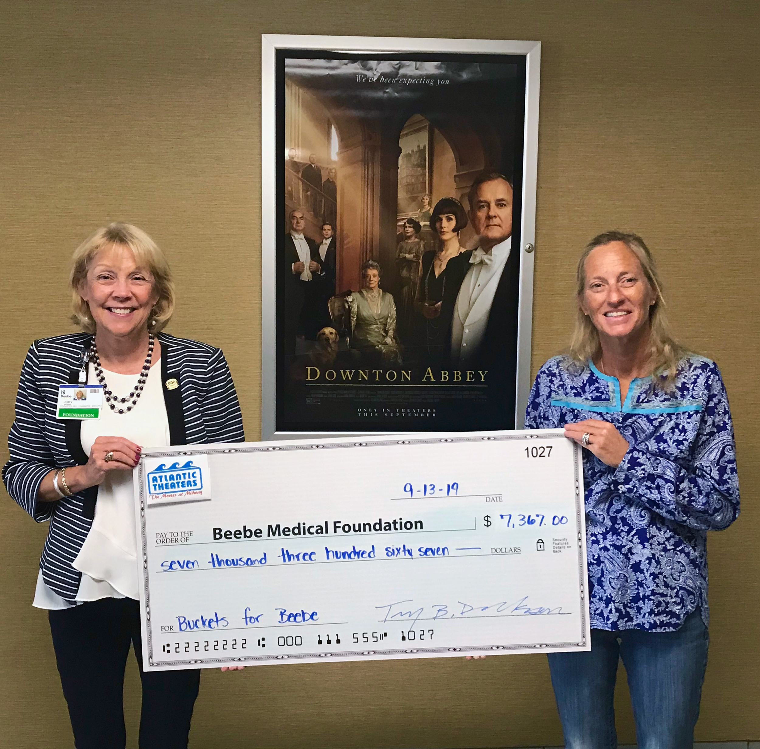 "Beebe Medical Foundation President and CEO, Judy Aliquo, accepts another donation from Tiffany Derrickson, Vice President of Atlantic Theaters from the Movies at Midway ""Buckets for Beebe"" program."