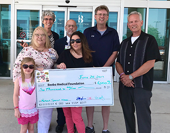 Shown during the check presentation (left to right) are Cast For A Cure organizers Brandy Timmons, with daughter Brooke, Clark Evans, and Scott Mayhugh present Beebe Medical Foundation with proceeds from the annual surf-fishing tournament to Beebe Heatlhc