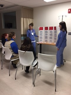 "First-year student Olivia Goldschmidt and senior Rebecca Tillman play a game of ""Stroke Jeopardy"" with an eager group of Girl Scouts."