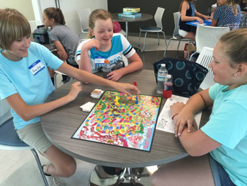 Ainsley Bell, Keelie Conaway, and Makeni Whaley practice playing board games on their lunch break.
