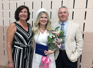 Margaret H. Rollins Student Philanthropy Award winner, Mallory Drew, shares a proud moment during the Margaret H. Rollins School of Nursing graduation with her aunt and uncle, Kerry and Clint Perkinson.