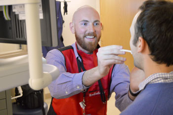Nick Bollinger works with a patient on a swallow test.
