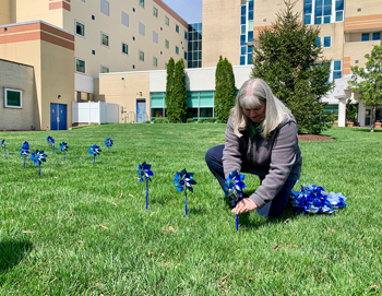 Beebe team member Sonia Manning places a pinwheel on the front lawn of the Margaret H. Rollins Lewes Campus on Tuesday, April 16.