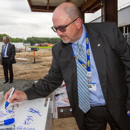 Rick Schaffner signs the beam at the South Coastal Health Campus near Millville.