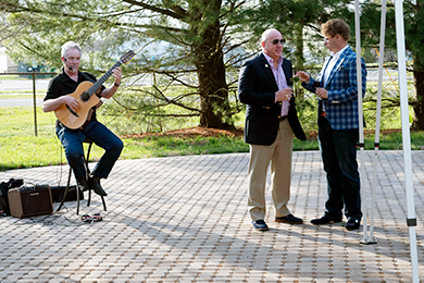 Paul Cullen performs as Tom Protack, Vice President of Development, and Andy Staton speak during the Beebe Medical Foundation patio party.