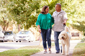Couple walks their dog in a neighborhood to boost metabolism.