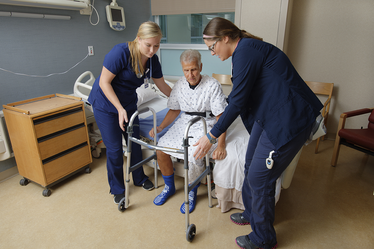 Orthopaedics patient receives help standing up to prevent a fall.