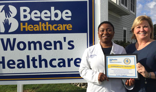Dr. Adeline Nukuna, left, receives a Celebrate Excellent Care plaque from Kristan Trugman in front of Beebe Women's Healthcare – Plantations, Lewes.