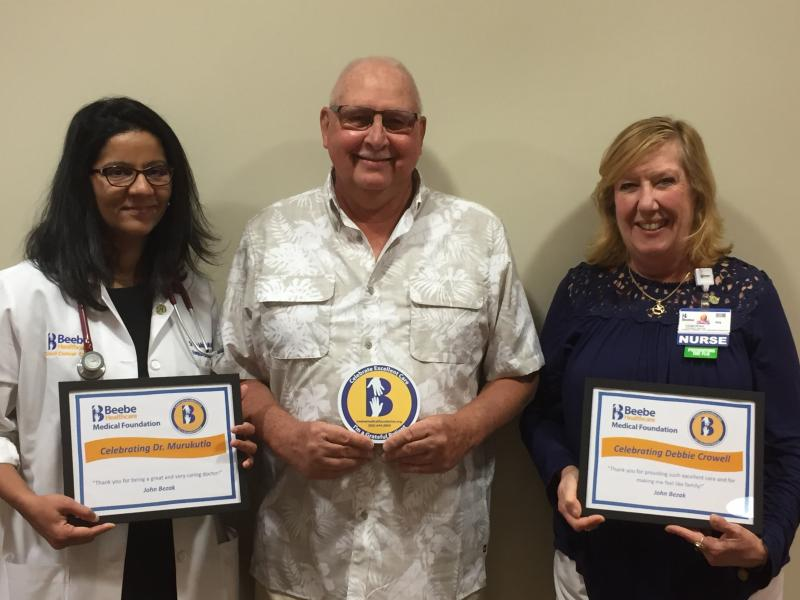 John Bezak celebrates the excellent oncological care he continues to receive from Beebe Healthcare's Tunnell Cancer Center Medical Oncologist Dr. Srujitha Murukutla, left, and Nurse Debbie Crowell.