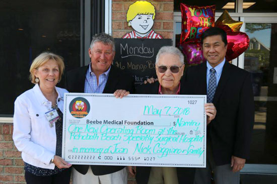 "Outside of the Nicola Pizza on Rehoboth Avenue, with ""Mama Nicola,"" Joan Caggiano, looking over everyone from above. Nick Caggiano and his son, Nick Jr., present a large check to Judy Aliquo, President of the Beebe Medical Foundation and Dr. Wilson C. Cho"