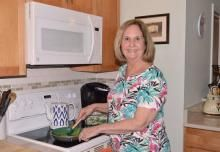 Beth Reynolds sautes spinach at home in Angola near Lewes, Del.