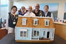 This Baltimore Colonial dollhouse built by Beebe volunteer Grant Kingswell will be auctioned Nov. 17 at the Beebe Ball to raise funds for Tunnell Cancer Center. Shown are (l-r) volunteer Lil Giuliano, Customer Service Liaison Candi Corsiglia, Executive Di