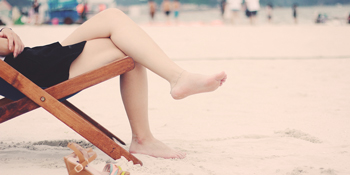 Woman sitting on beach with tired legs - could it be venous insufficiency?